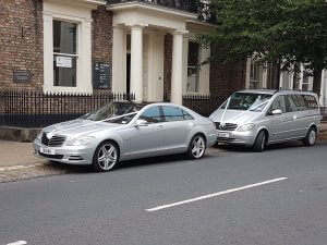 A Mercedes s class and a Mercedes Viano with ribbons and bows outside York registry office
