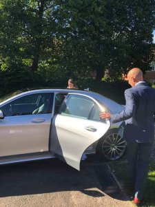 Chauffeur Mark Heaney helping a customer in to our Mercedes s class